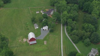AX78_054 - 5K stock footage aerial video flying away from a red barn and rural house in Brookeville, Maryland