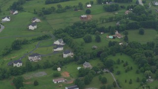 AX78_058 - 5K stock footage aerial video of rural homes near a pair of barns in Brookeville, Maryland