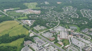 AX78_061 - 5K stock footage aerial video flying over shopping centers and suburban homes to approach a high school in Clarksville, Maryland