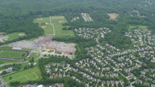 AX78_062 - 5K stock footage aerial video flying over suburban homes and River Hill High School toward forest, Clarksville, Maryland