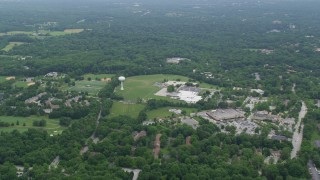 AX78_065 - 5K stock footage aerial video of Harper's Choice Middle School, Joseph Square Shopping Center, and suburban homes in Columbia, Maryland