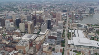 AX78_087 - 5K stock footage aerial video approaching Downtown Baltimore skyscrapers by the Baltimore Convention Center in Maryland