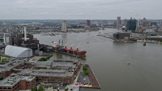 AX78_105 - 5K stock footage aerial video approaching Domino Sugar Factory and cargo ship beside Patapsco River, Maryland