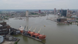 AX78_106 - 5K stock footage aerial video flying over cargo ship to approach Inner Harbor area of Downtown Baltimore, Maryland