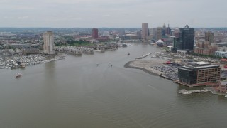 AX78_107 - 5K stock footage aerial video flying over Patapsco River to approach Inner Harbor and Downtown Baltimore, Maryland