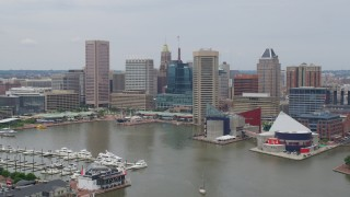 AX78_109 - 5K stock footage aerial video approaching Downtown Baltimore skyscrapers and Harborplace pavilions near National Aquarium, Maryland