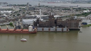 AX78_113 - 5K stock footage aerial video of Domino Sugar Factory and a docked cargo ship in Baltimore, Maryland