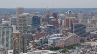 AX78_114 - 5K stock footage aerial video flying by skyscrapers and city buildings in Downtown Baltimore, Maryland