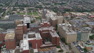 AX78_117 - 5K stock footage aerial video flying over Johns Hopkins Hospital buildings to approach urban neighborhoods in Baltimore, Maryland