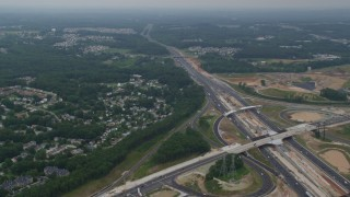 AX78_132 - 5K stock footage aerial video flying over suburban homes beside I-95 with light traffic in Baltimore, Maryland