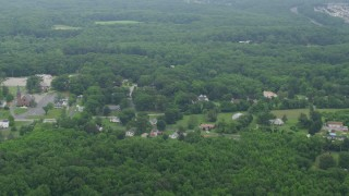 AX78_137 - 5K stock footage aerial video flying over power lines to approach rural homes and forest in Kingsville, Maryland