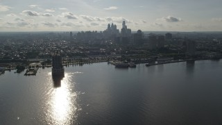 AX79_096 - 5K stock footage aerial video flying over Delaware River to approach Downtown Philadelphia skyline, Pennsylvania