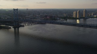 AX80_002 - 5K stock footage aerial video approaching Benjamin Franklin Bridge spanning the Delaware River, Philadelphia, Sunset