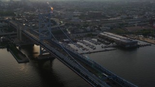 AX80_003 - 5K stock footage aerial video of the Benjamin Franklin Bridge beside a marina in Philadelphia, Pennsylvania, Sunset