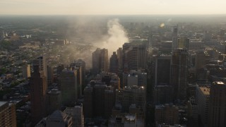 AX80_035 - 5K stock footage aerial video of residential fire near office buildings in Downtown Philadelphia, Pennsylvania, Sunset