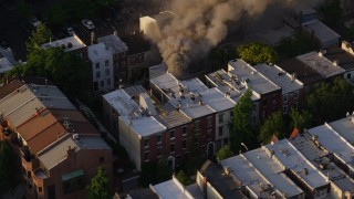 AX80_038 - 5K stock footage aerial video of smoke from a residential fire near Downtown Philadelphia, Pennsylvania, Sunset