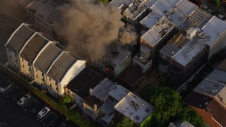 AX80_040 - 5K stock footage aerial video tilting to a bird's eye view of smoke and fire from an urban home in Philadelphia, Pennsylvania, Sunset