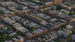 AX80_052 - 5K stock footage aerial video flying by row houses in North Philadelphia, Pennsylvania, Sunset