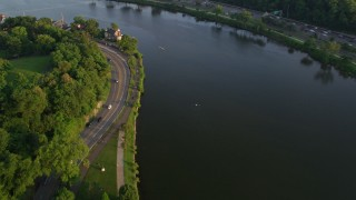 AX80_054 - 5K stock footage aerial video panning across the Schuylkill River to reveal Boathouse Row, Philadelphia, Pennsylvania, Sunset