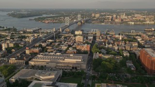 AX80_059 - 5K stock footage aerial video flying over office buildings and by Benjamin Franklin Bridge, Philadelphia, Pennsylvania, Sunset
