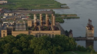 AX80_073 - 5K stock footage aerial video of an abandoned factory by the Delaware River, North Philadelphia, Pennsylvania Sunset