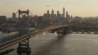 AX80_075E - 5K stock footage aerial video of Benjamin Franklin Bridge and Downtown Philadelphia skyline, Pennsylvania, Sunset