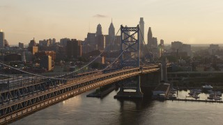 AX80_076 - 5K stock footage aerial video approaching Benjamin Franklin Bridge and the Downtown Philadelphia skyline, Pennsylvania Sunset