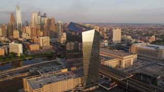 AX80_085 - 5K stock footage aerial video orbiting Cira Centre and reveal the Downtown Philadelphia skyline, Pennsylvania, Sunset