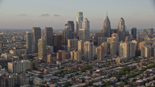 AX80_092E - 5K stock footage aerial video of Downtown Philadelphia skyscrapers and urban neighborhoods in Pennsylvania, Sunset