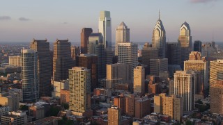 AX80_094 - 5K stock footage aerial video flying over Downtown Philadelphia to approach its tallest skyscrapers, Pennsylvania, Sunset