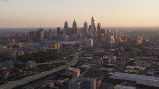 AX80_098 - 5K stock footage aerial video of Downtown Philadelphia skyscrapers behind the I-676 freeway, Pennsylvania, Sunset