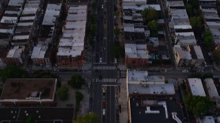 AX80_112 - 5K stock footage aerial video tilting from Broad Street and urban South Philly neighborhood to reveal Downtown Philadelphia skyline, Pennsylvania, Sunset