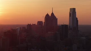 AX80_130 - 5K stock footage aerial video of the setting sun behind the Downtown Philadelphia skyline, Pennsylvania, Sunset
