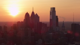 AX80_131 - 5K stock footage aerial video of Downtown Philadelphia skyline with the setting sun in the background, Pennsylvania, Sunset