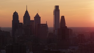 AX80_133 - 5K stock footage aerial video of the silhouette of the Downtown Philadelphia skyline, Pennsylvania, Sunset