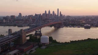 AX80_136 - 5K stock footage aerial video approaching the Benjamin Franklin Bridge over Delaware River, Downtown Philadelphia skyline, Pennsylvania, Sunset