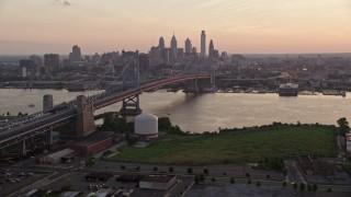 AX80_136E - 5K stock footage aerial video fly next to the Benjamin Franklin Bridge over Delaware River toward Downtown Philadelphia skyline, Pennsylvania, Sunset