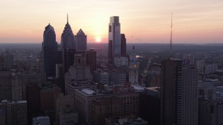 AX80_152 - 5K stock footage aerial video of Downtown Philadelphia skyscrapers and the setting sun in the background, Pennsylvania, Sunset