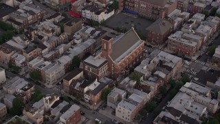 AX80_158 - 5K stock footage aerial video of Saint Paul Church in an urban neighborhood, South Philadelphia, Pennsylvania, Sunset