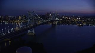 AX81_007E - 5K stock footage aerial video approaching Benjamin Franklin Bridge, Delaware River, and Downtown Philadelphia skyline, Pennsylvania, Night