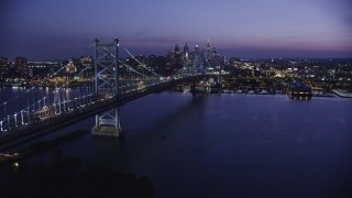 AX81_008 - 5K stock footage aerial video approaching Benjamin Franklin Bridge, Delaware River, and Downtown Philadelphia skyline, Pennsylvania, Night
