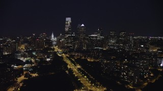 AX81_036 - 5K stock footage aerial video following Benjamin Franklin Parkway toward City Hall and Downtown Philadelphia skyline, Pennsylvania, Night