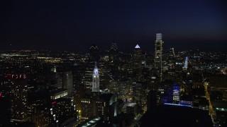 AX81_040E - 5K stock footage aerial video fly away from Philadelphia City Hall to reveal Downtown Philadelphia skyscrapers, Pennsylvania, Night