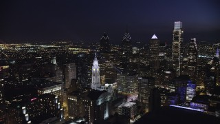 AX81_041 - 5K stock footage aerial video of a reverse view of Downtown Philadelphia skyscrapers and City Hall, Pennsylvania, Night