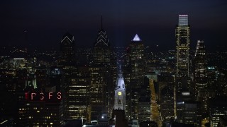AX81_042 - 5K stock footage aerial video flying by City Hall clock tower with tall Downtown Philadelphia skyscrapers behind it, Pennsylvania, Night