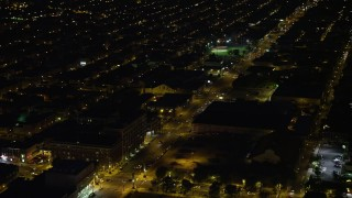 AX81_044 - 5K stock footage aerial video of city streets and dark warehouse building in South Philadelphia, Pennsylvania, Night