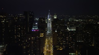 AX81_046 - 5K stock footage aerial video following Broad Street to approach Philadelphia City Hall, Downtown Philadelphia, Pennsylvania, Night