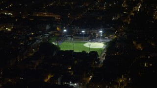AX81_060 - 5K stock footage aerial video of baseball field in an urban neighborhood in South Philadelphia, Pennsylvania, Night