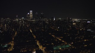 AX81_080 - 5K stock footage aerial video flying by Downtown Philadelphia skyscrapers and Broad Street leading to City Hall, Pennsylvania, Night