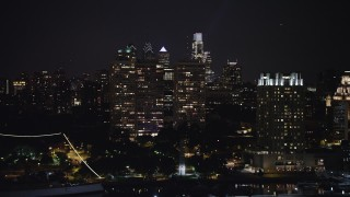 AX81_092 - 5K stock footage aerial video of Downtown Philadelphia skyline and apartment complexes seen from the historic ship Moshulu, Pennsylvania, Night